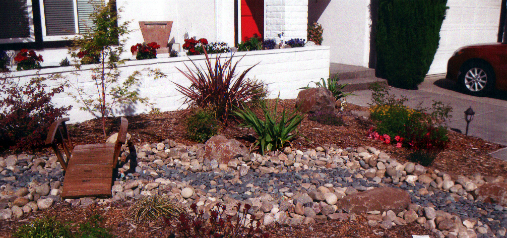 Create your own oasis with rocks. This is demonstrated with Noyio Cobbles and River Rock to mimic a water feature. The Brige was handmade out of wine barrels.