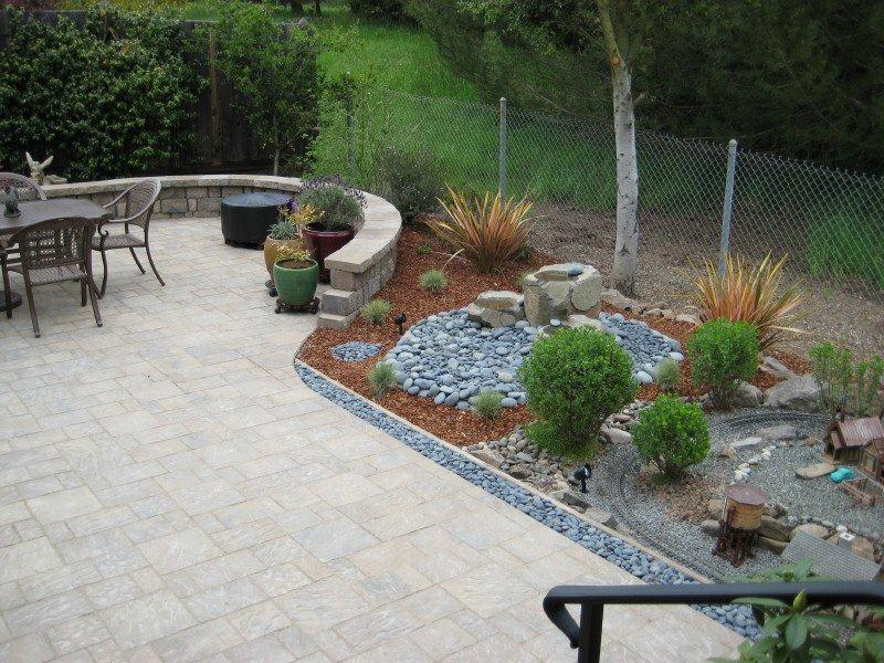 Patio with miniature railroad in back yard using Sequoia Landscape Supplies.
